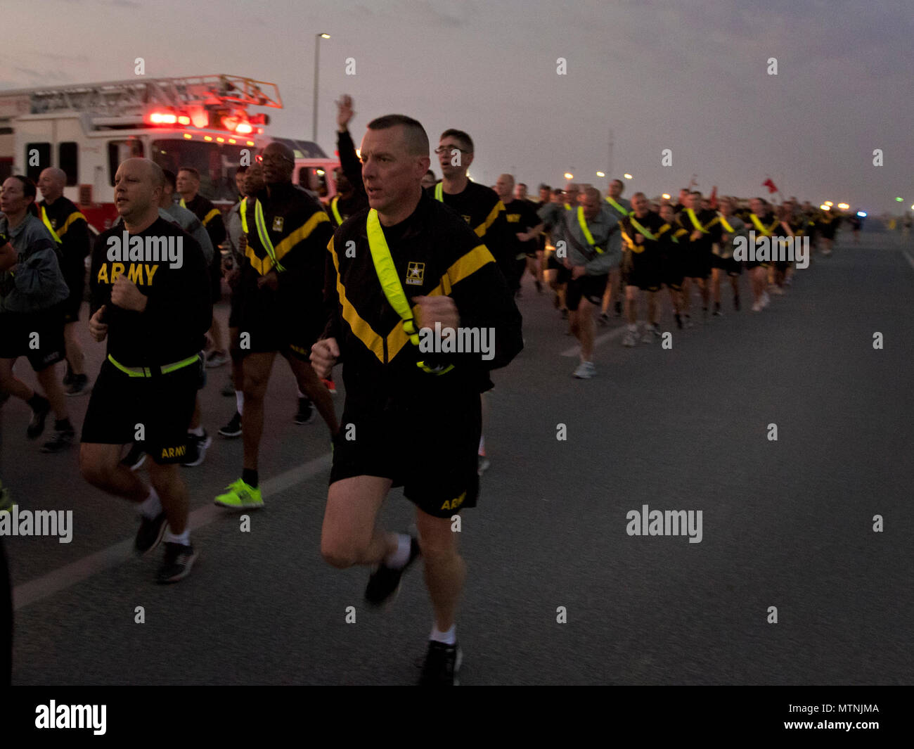 1st Sgt. Brian Jarvis, 316th Sustainment Command (Expeditionary) Headquarters and Headquarters Company 1st Sgt., calls cadences during a 5K at Camp Arifjan, Kuwait, Jan. 10, 2017. (U.S. Army Photo by Staff Sgt. Dalton Smith) - Stock Image