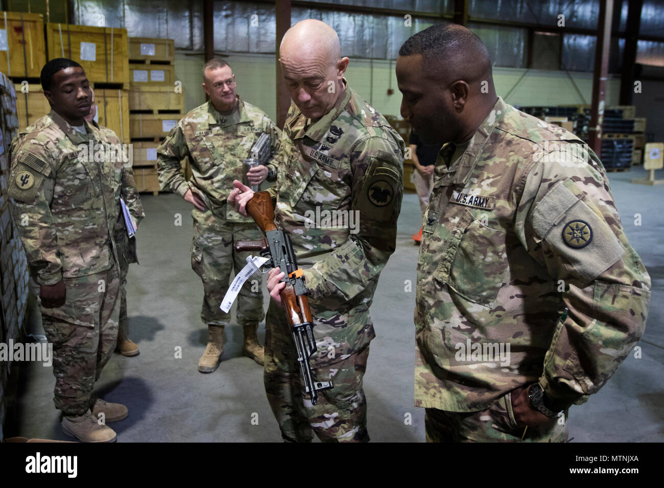 U.S. Army Reserve Commanding General, Lt. Gen. Charles D. Luckey, inspects an AK-47 rifle during a tour of the Iraq Train and Equipment Fund (ITEF) warehouse at Camp Arifjan, Kuwait, Jan. 4, 2017. (U.S. Army Photo by Staff Sgt. Dalton Smith) - Stock Image