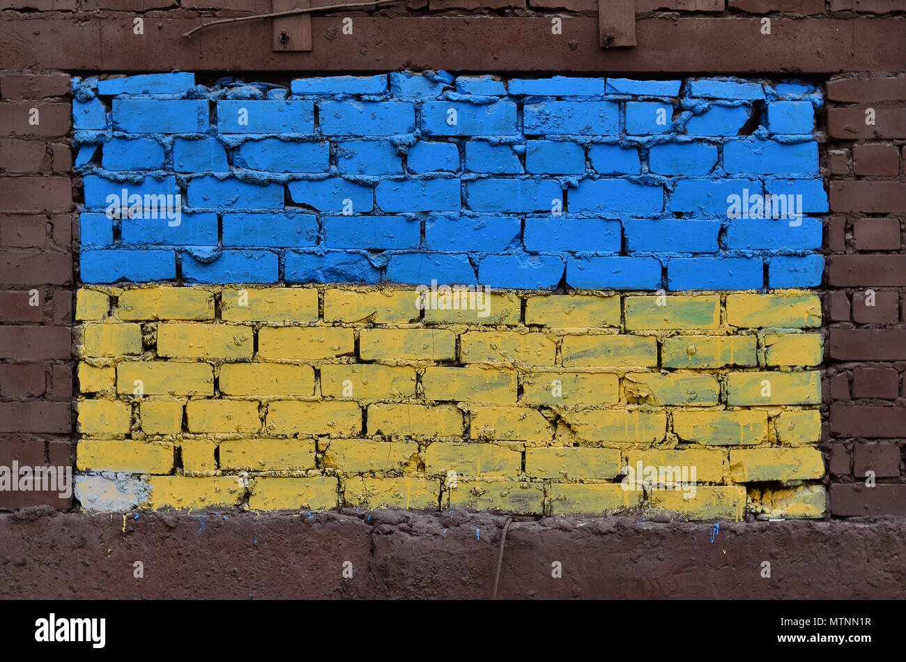 An old brick wall painted in the colors of the Ukrainian flag ...