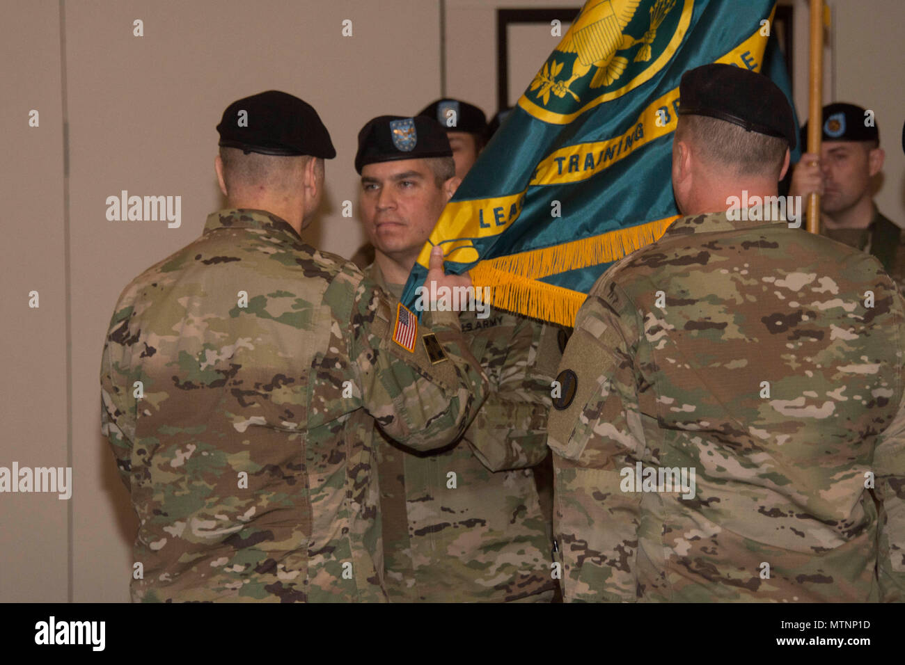 Col. Fernando Guadalupe Jr., commander of the Leader Training Brigade, receives the unit colors from Maj. Gen. Anthony C. Funkhouser, Center of Initial Military Training commander during a change of command ceremony Jan. 6 at the Officers Club on Fort Jackson. Guadalupe took command of the unit from Col. Michael Mammay who is retiring. (U.S. Army photo by Robert Timmons, Fort Jackson Public Affairs/Released) Stock Photo