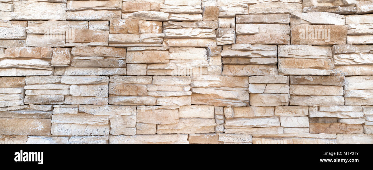 Coarse wall of elongated stones - Stock Image