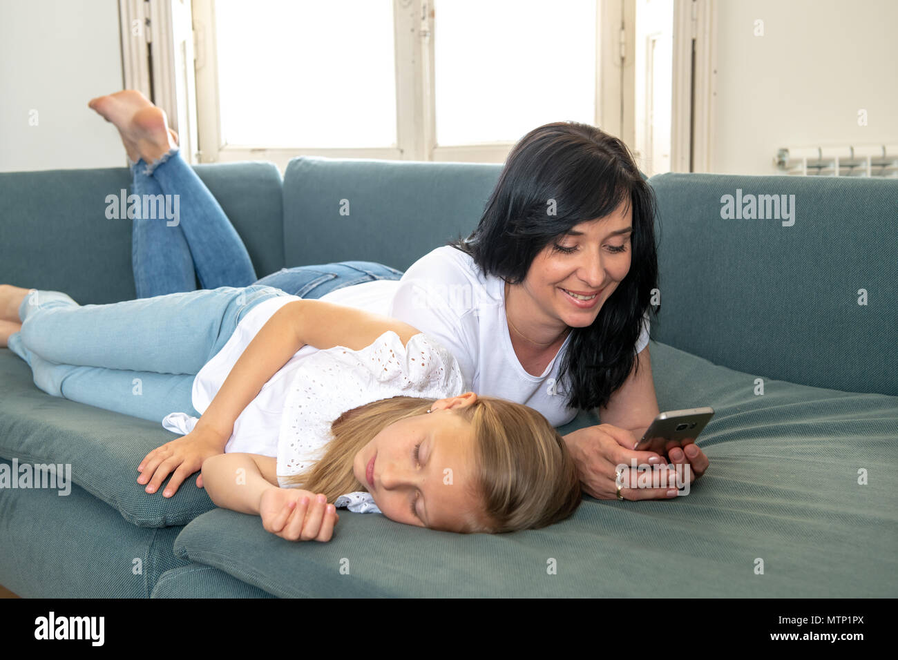 Digital technology addicted mum using her smart phone ignoring her sad Little girl feeling abandoned and unhappy with her mum not paying attention to  - Stock Image