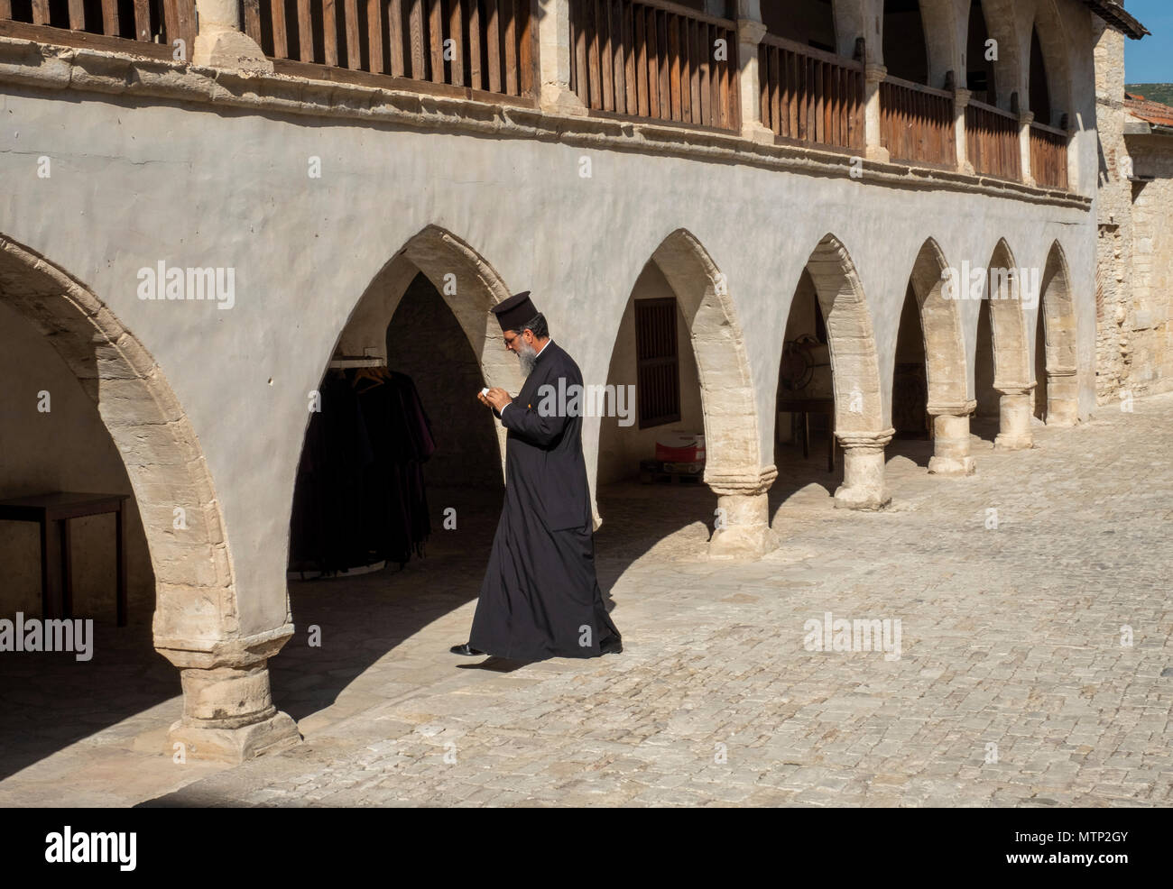 A priest walking across a courtyard at the Monastery of the Holy Cross, Omodos village, Cyprus. - Stock Image