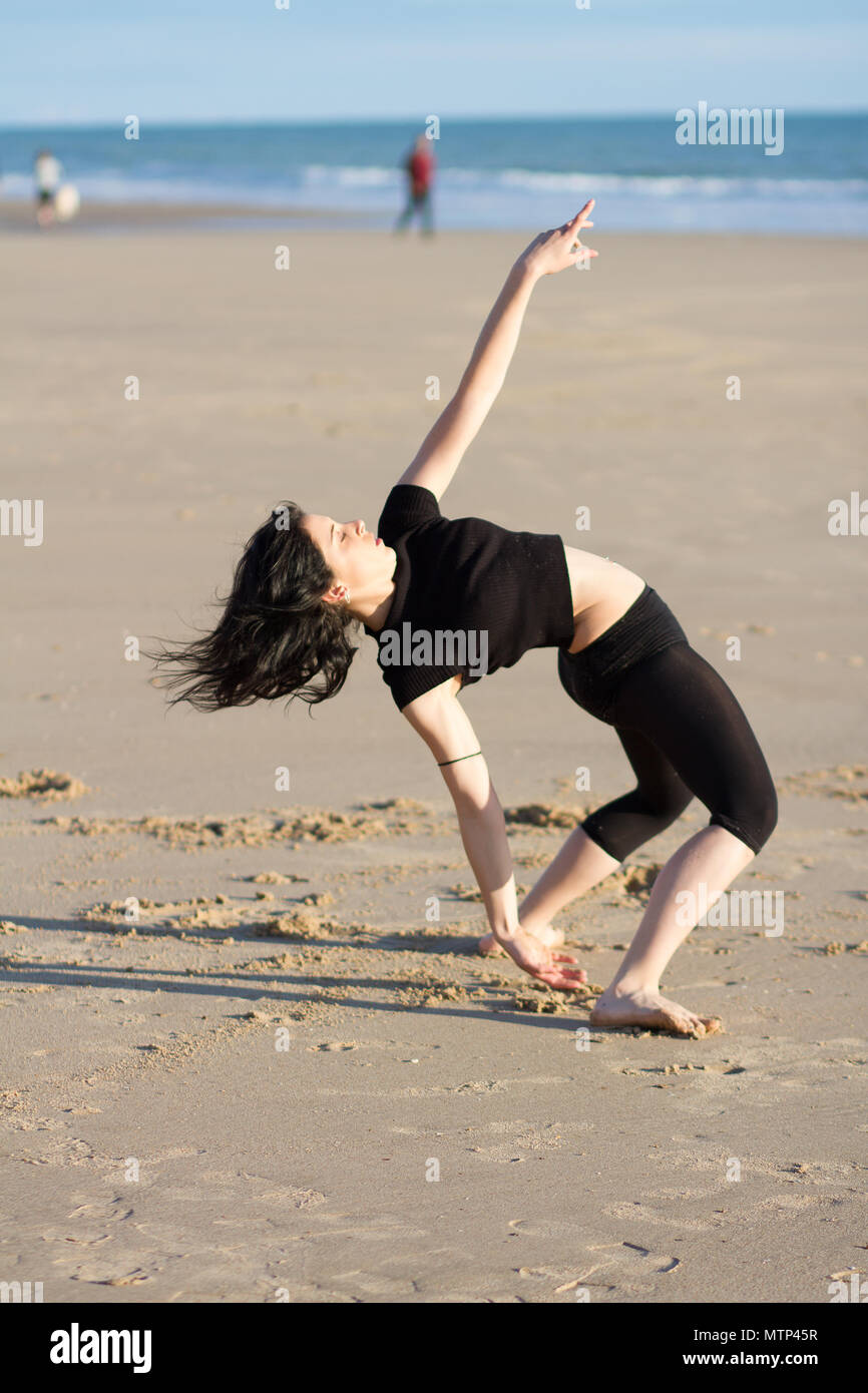 Dancer on the beach sunset time, free choreography - Stock Image