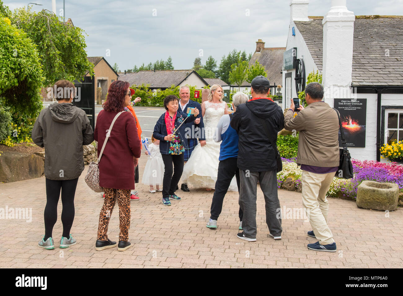 Asian tourists taking selfies and photographs of a bride arriving for her wedding at Gretna Green, Scotland, UK - Stock Image