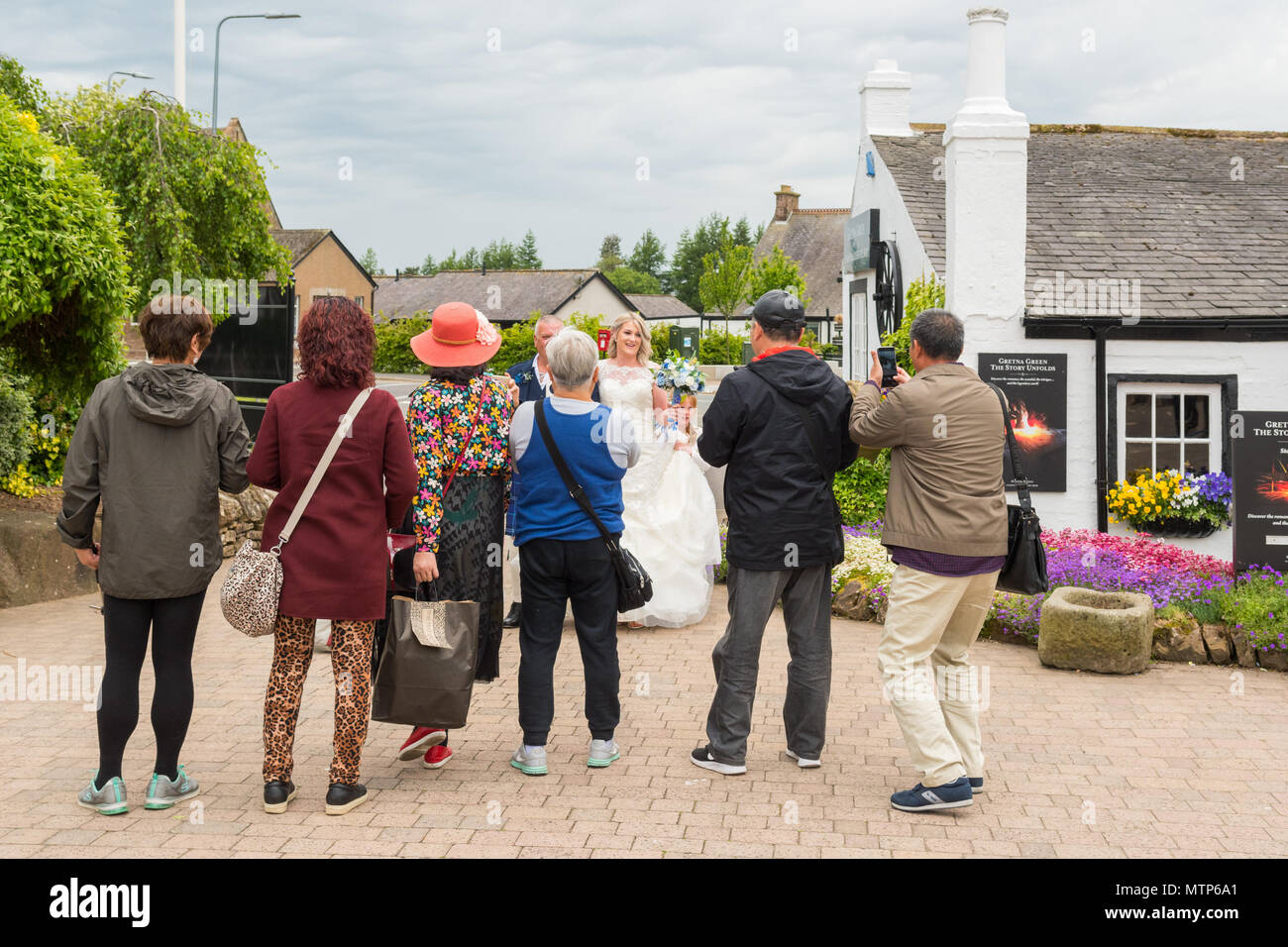 Asian tourists taking photographs of a bride arriving for her wedding at Gretna Green, Scotland, UK - Stock Image