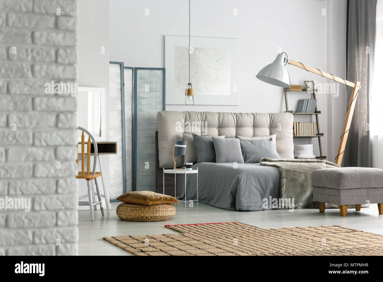 Cozy grey bedroom in modern loft with white brick wall Stock Photo ...