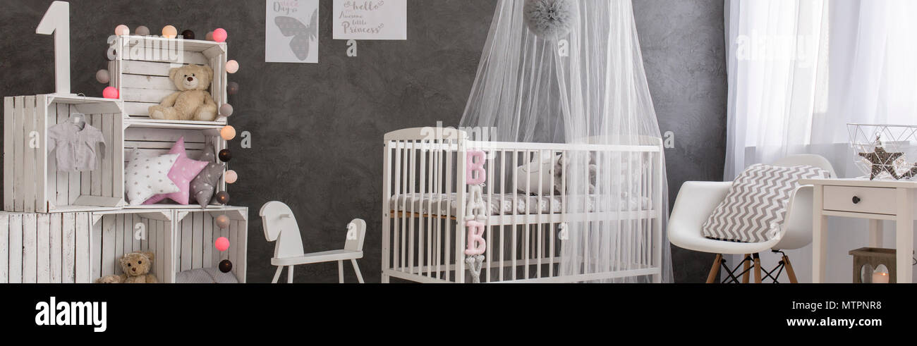 Baby room with white cot, handmade shelving unit and stylish decorations - Stock Image