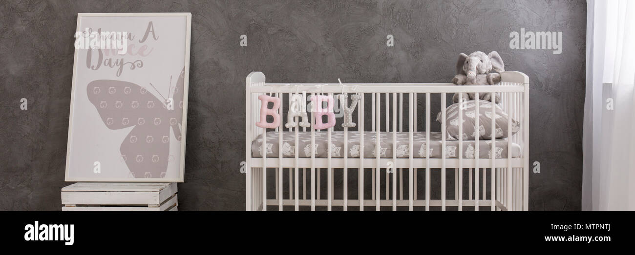 Panoramic photo of a white baby crib standing by a grey stucco wall - Stock Image