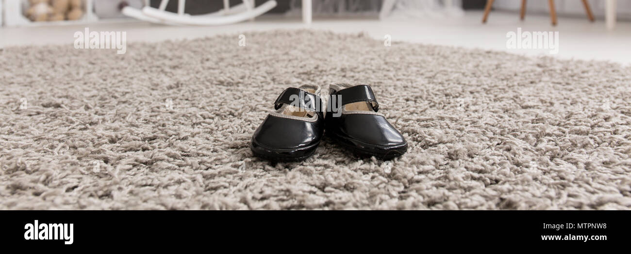 Close-up of newborn girl's shoes on a fluffy beige carpet in a bright baby room - Stock Image