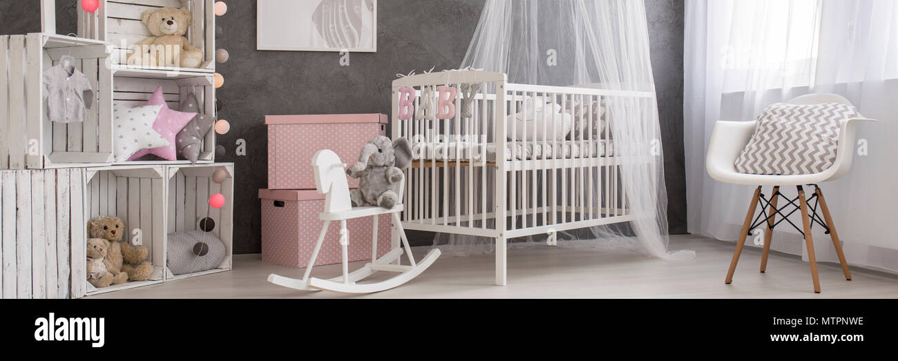 Pastel baby girl's room with a white canopy cot and a rocking horse - Stock Image