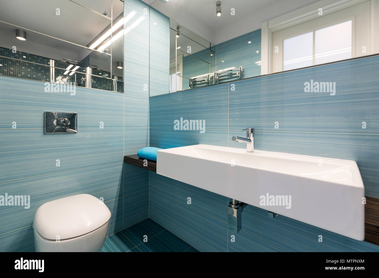 Spacious bathroom with big basin and toilet, blue tiles and mirrors ...