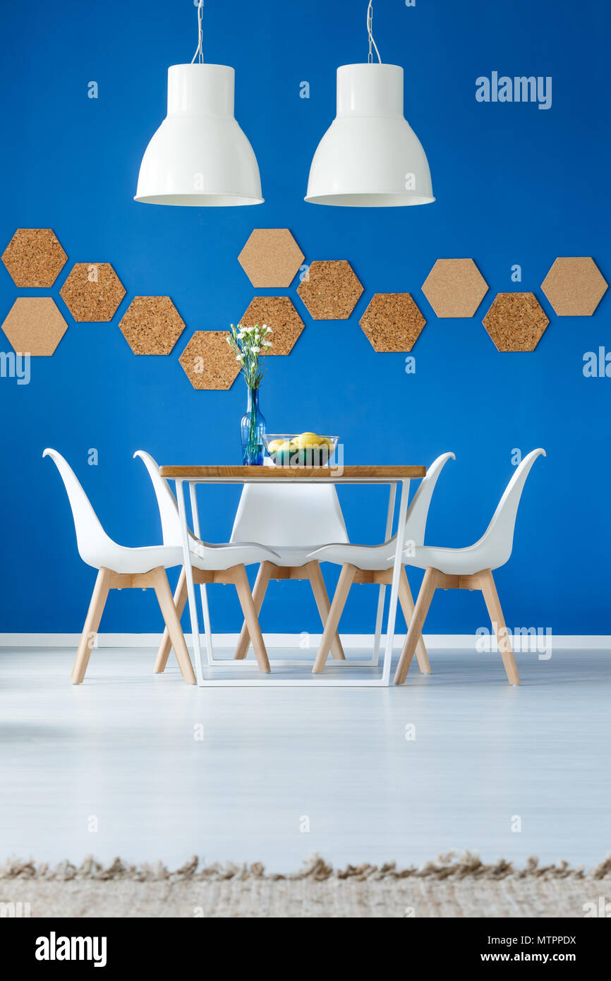 Royal blue dining room inspiration with natural accessories and wooden and white furniture in scandinavian design