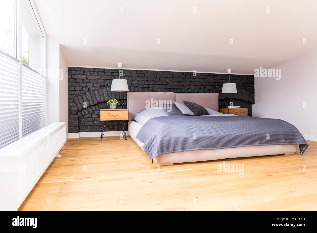 King-size bed with blue overlay in simple bedroom with black brick ...