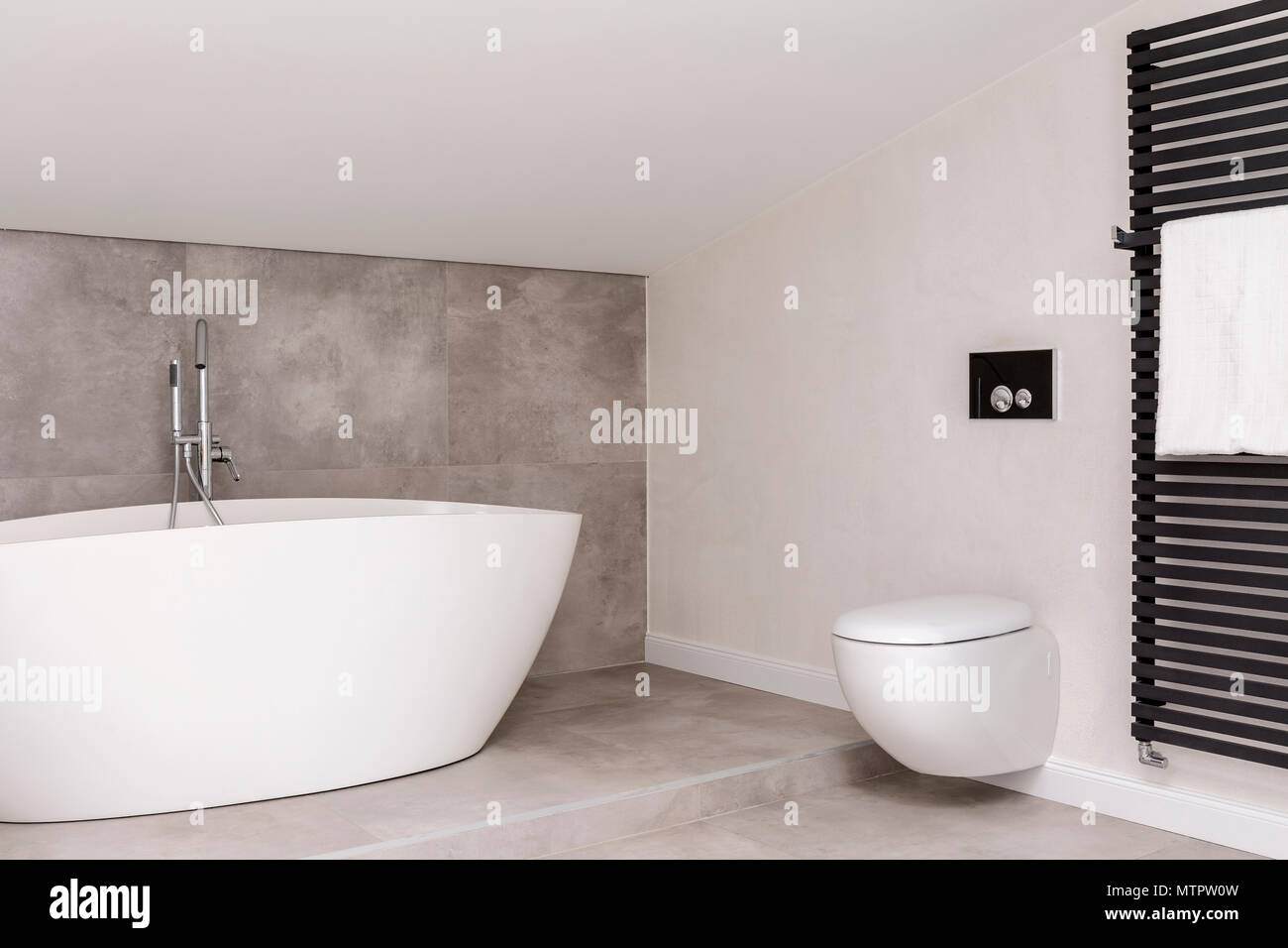 White bathtub against grey glaze in simple bathroom with toilet and ...