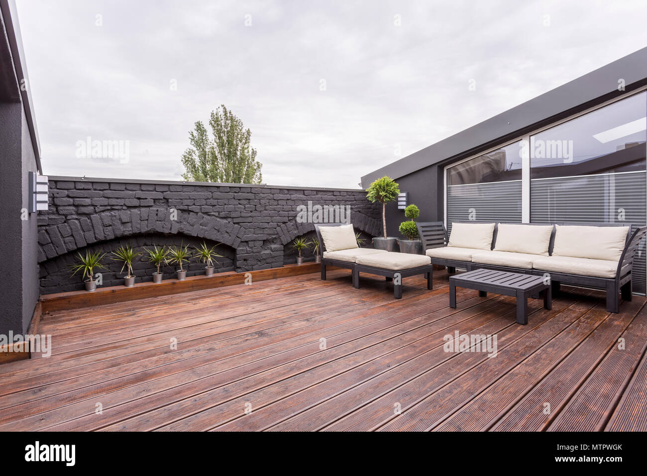 Plants and beige garden furniture on terrace with wooden floor and black brick wall - Stock Image