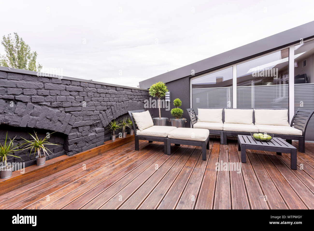 Apples in bowl on black wooden coffee table on terrace with garden furniture and brick wall - Stock Image