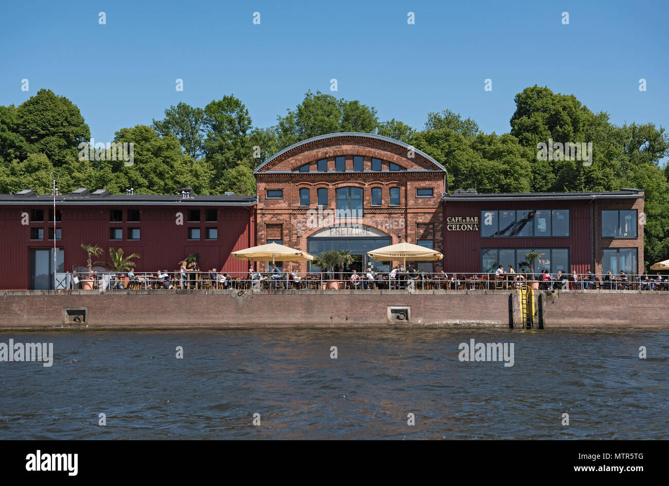 cafe with guests on the bank of the trave river in lubeck, germany - Stock Image