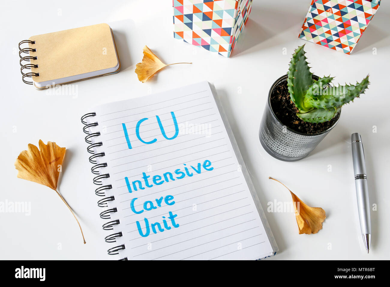 ICU Intensive care unit written in a notebook on white table - Stock Image