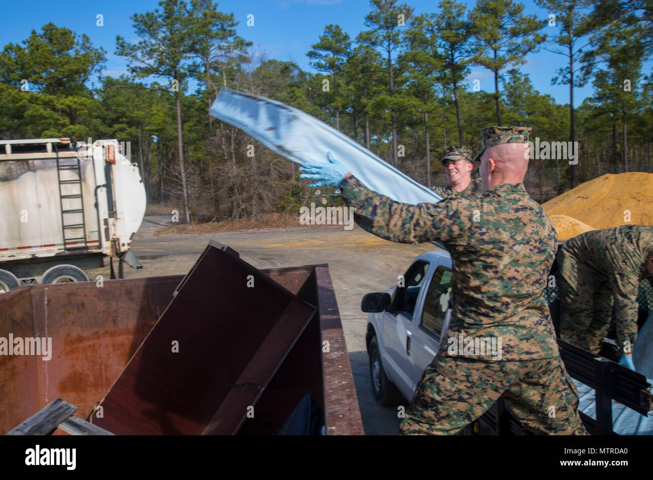 U.S. Marines with Headquarters and Support Battalion, Marine Corps Installation East, dispose of trash, Camp Lejeune, N.C., Jan. 12, 2017. The clean sweep was conducted to ensure a good state of cleanliness is being maintained within the units' respected facilities. (U.S. Marine Corps photo by Lance Cpl. Austin Livingston) - Stock Image