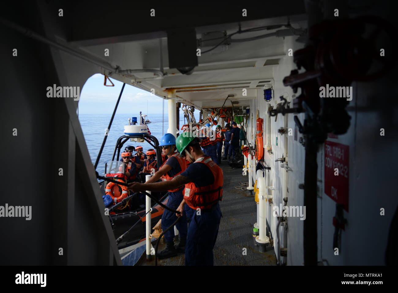 EASTERN PACIFIC OCEAN – Crewmembers from the Coast Guard Cutter Sherman recover the cutter's small boat, Jan. 9, 2017. Sherman, homeported in Honolulu, is on counter narcotics mission in the Eastern Pacific Ocean. Cutters like Sherman routinely conduct operations from South America to the Bering Sea conducting alien migrant interdiction operations, domestic fisheries protection, search and rescue, counter-narcotics and other Coast Guard missions at great distances from shore keeping threats far from the U.S. mainland. (FOR RELEASE U.S. Coast Guard photo Chief Warrant Officer Allyson E.T. Conro - Stock Image