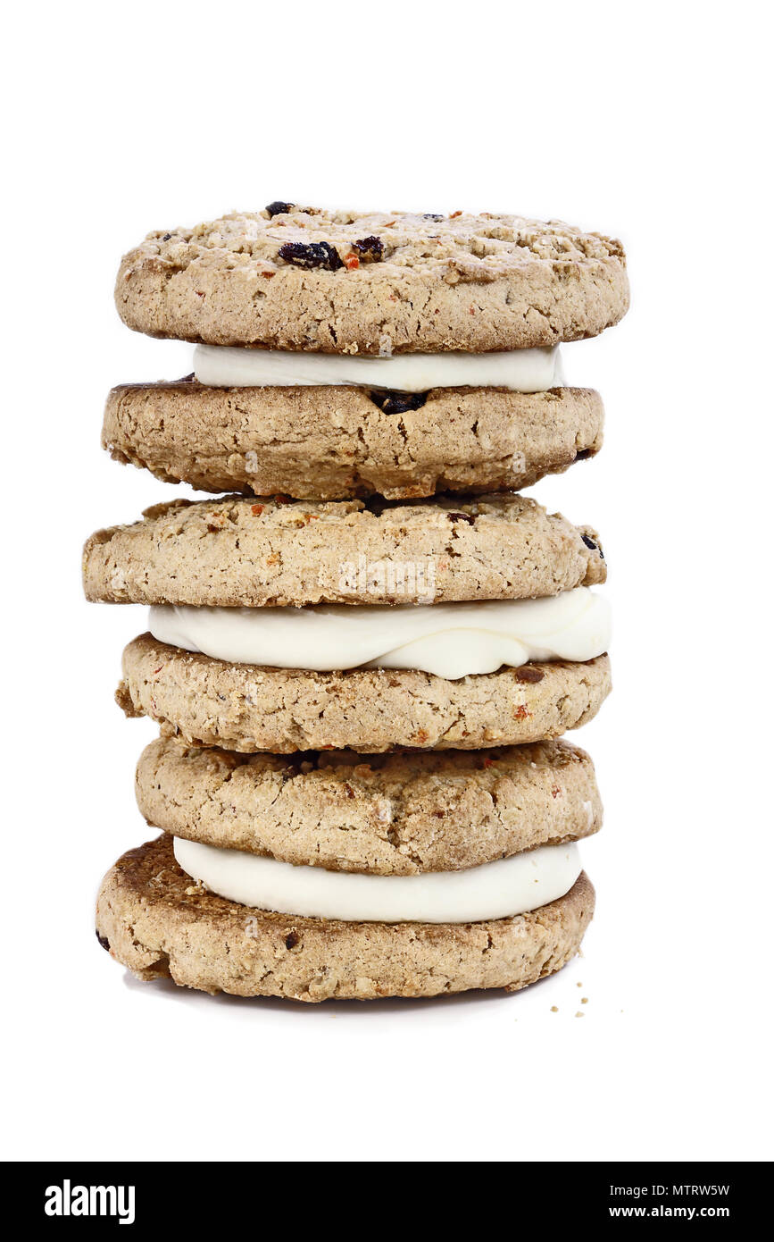 Carrot cake cookies sandwiches stuffed with cream cheese icing isolated over a white background with light shadow. - Stock Image