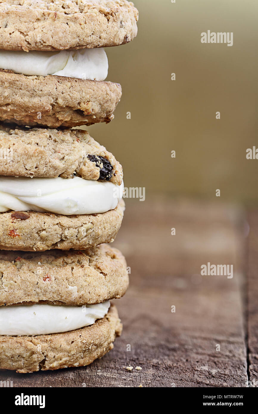 Macro stack of carrot cake raisin cookies sandwiches stuffed with cream cheese icing. Free space for copy text background. - Stock Image