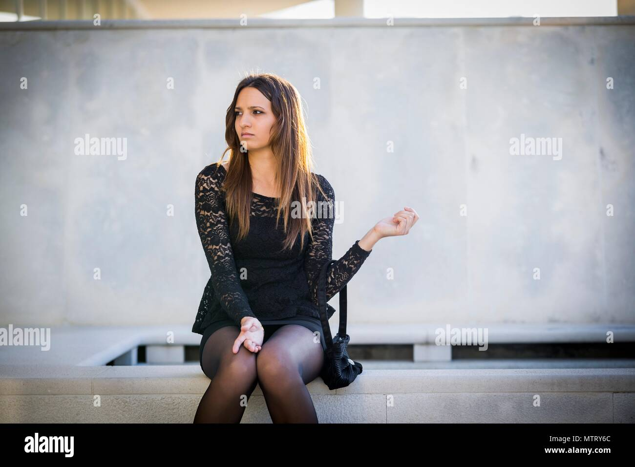 Young woman legs heels looking away serious and concerned distrust - Stock Image