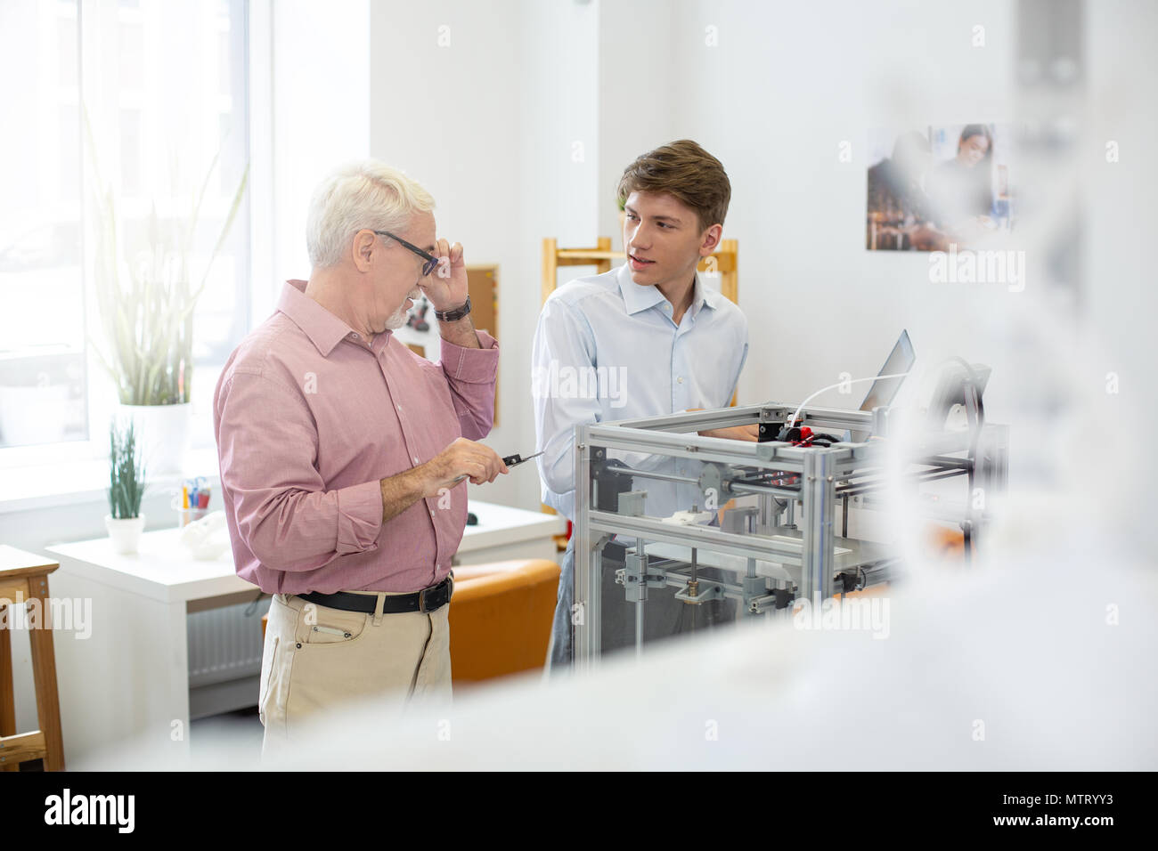 Pleasant intern talking with his supervisor while printing 3D models - Stock Image