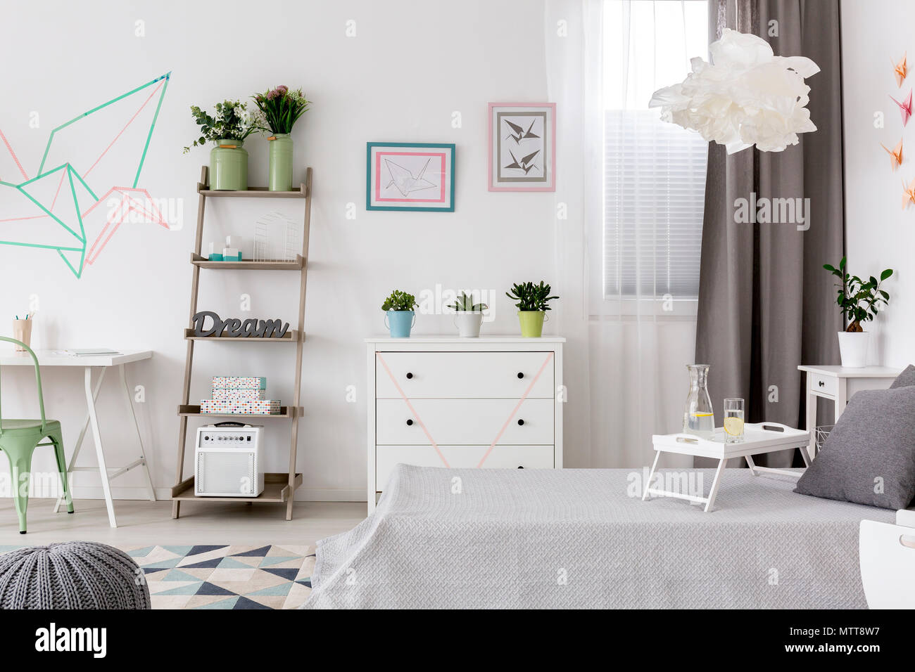 Light bedroom and office combined and creative wall decor - Stock Image