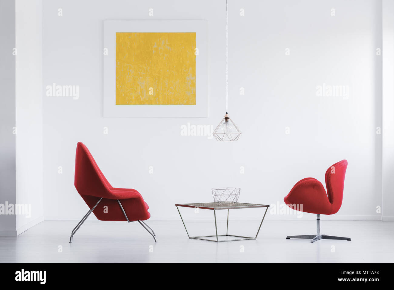 Modern Red Armchairs Standing By The Table With Metal Bowl In White Interior
