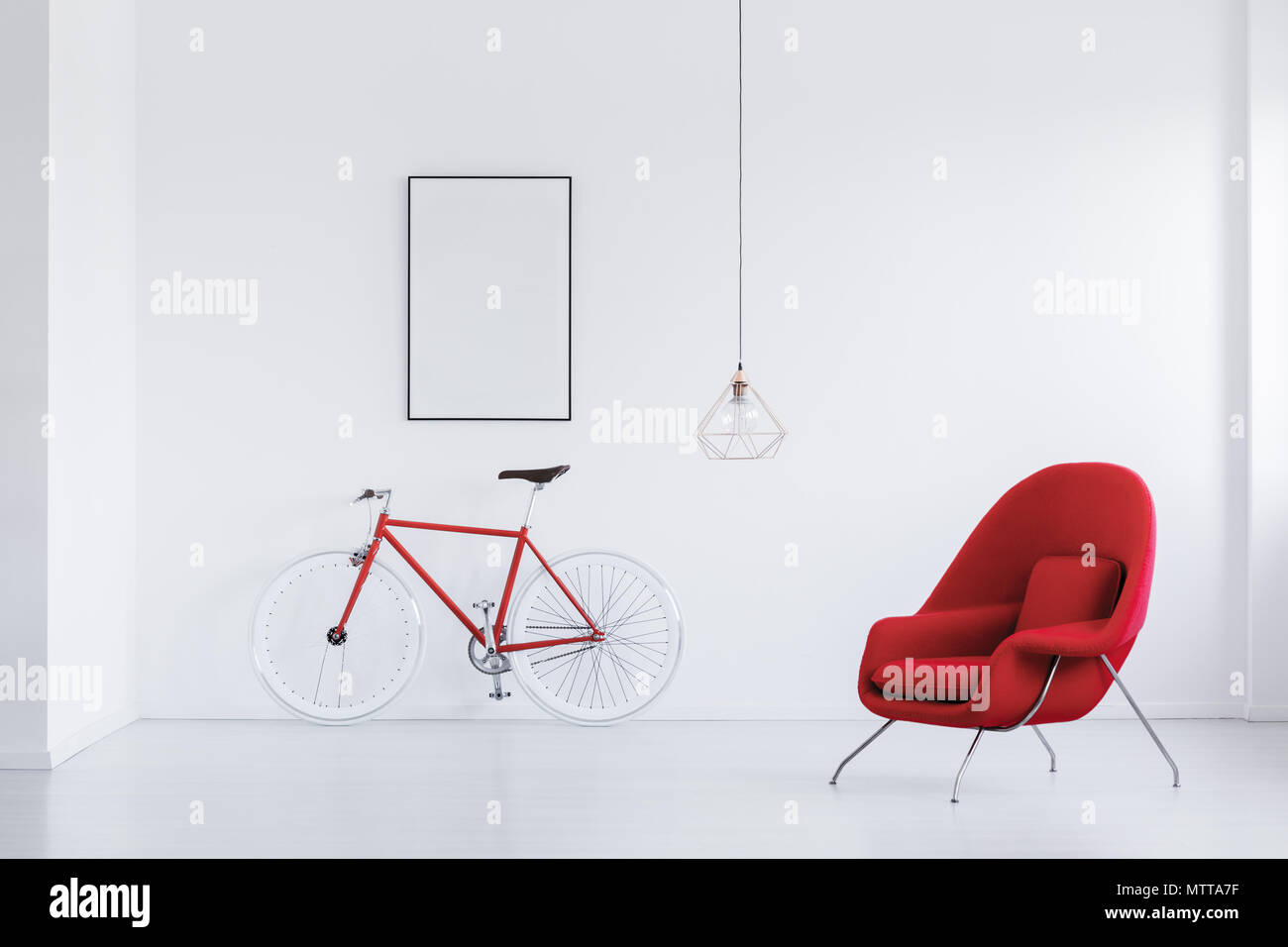 Red and white hipster bicycle standing in white room with comfy armchair and mockup poster - Stock Image