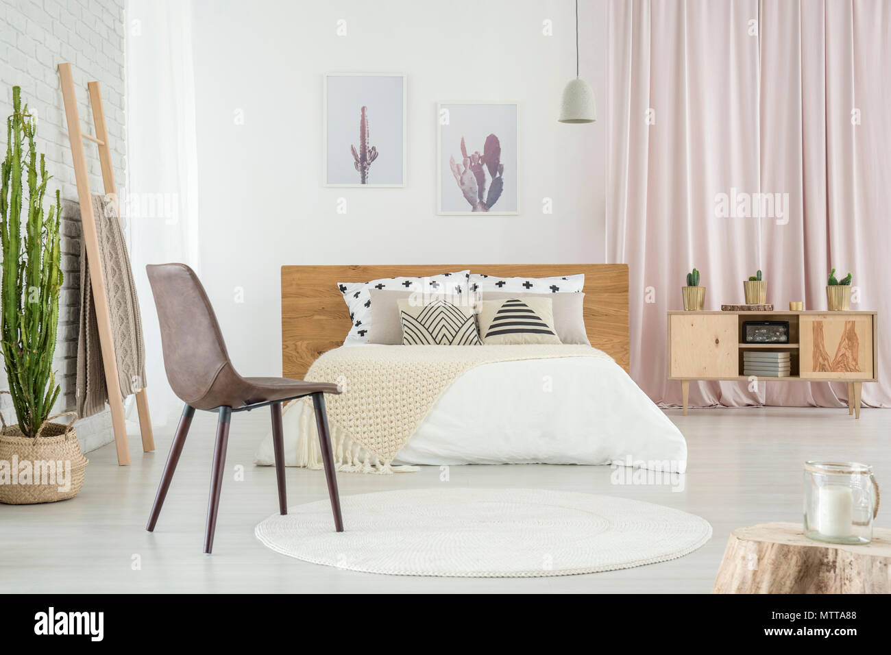 White round carpet on the floor in room with bed, patterned pillows ...