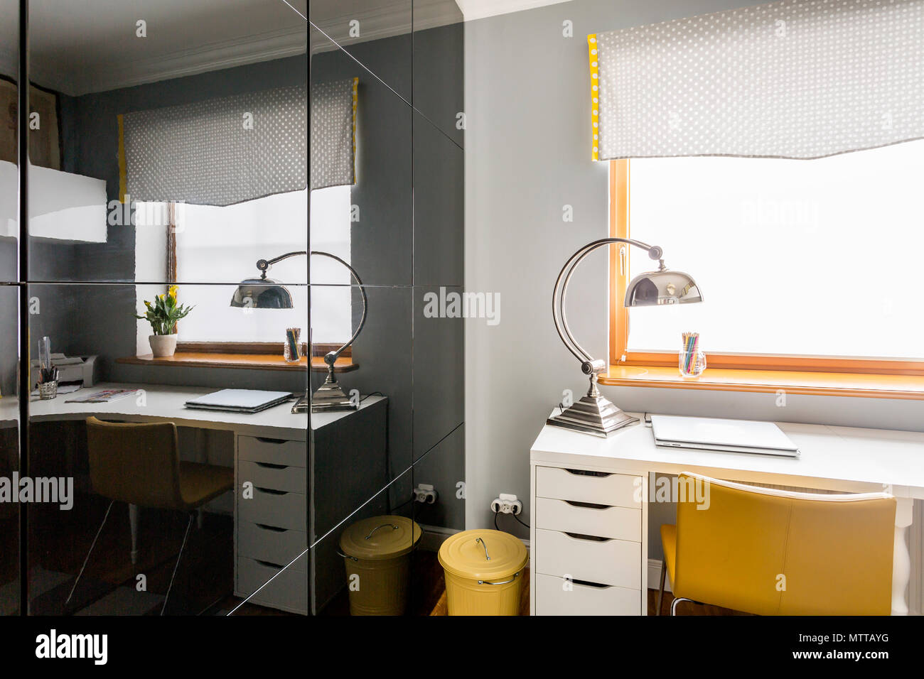 Stylish study room with black glass sliding wardrobe doors, white desk, yellow chair and modern lamp Stock Photo