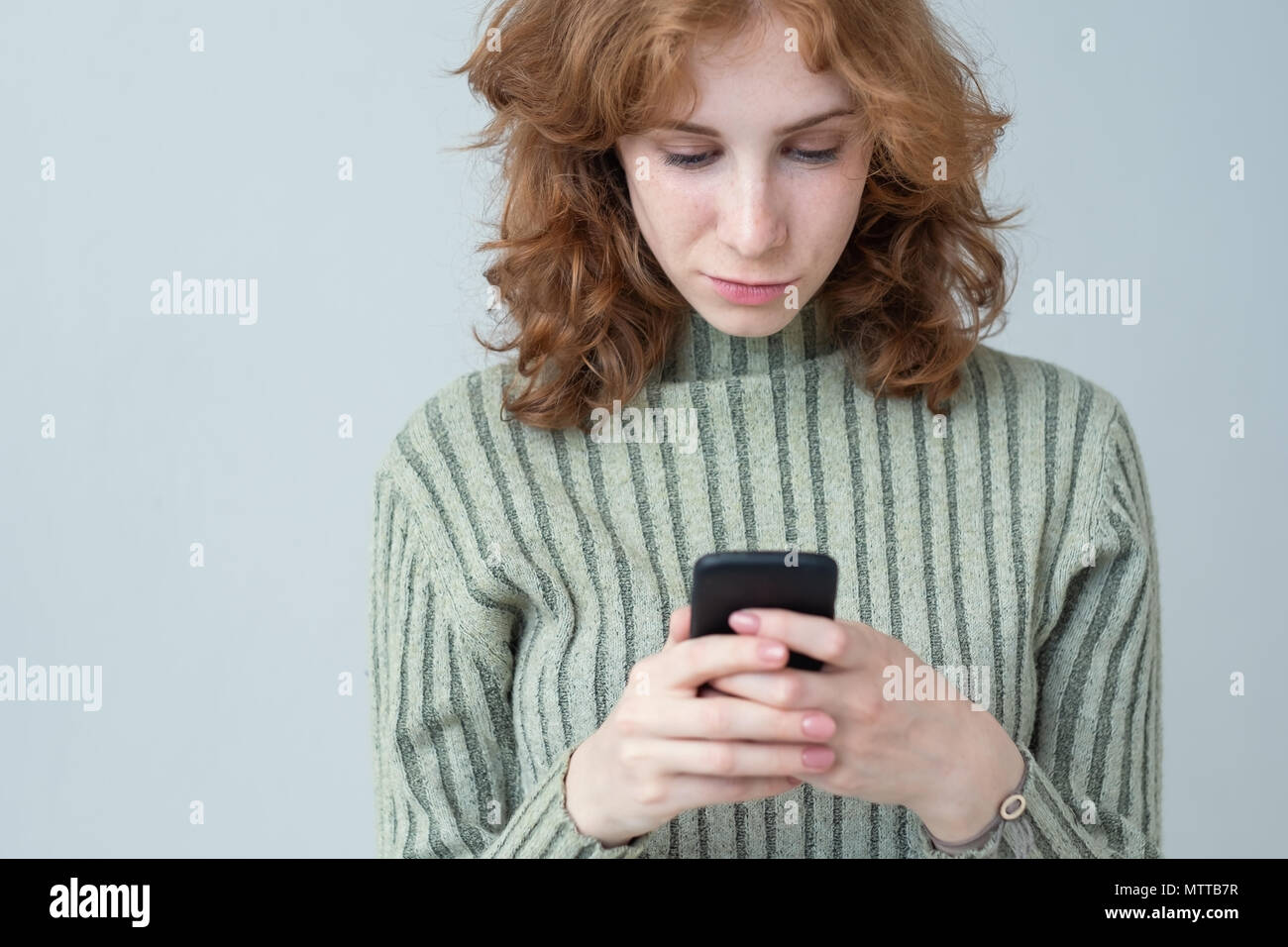 Pretty caucasian girl with red hair sending sms - Stock Image