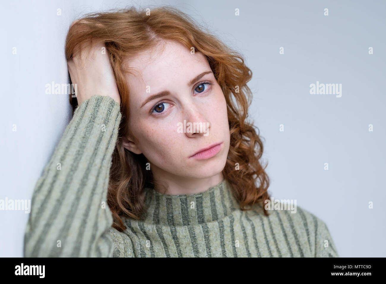 Young disappointed woman with red curly hair - Stock Image