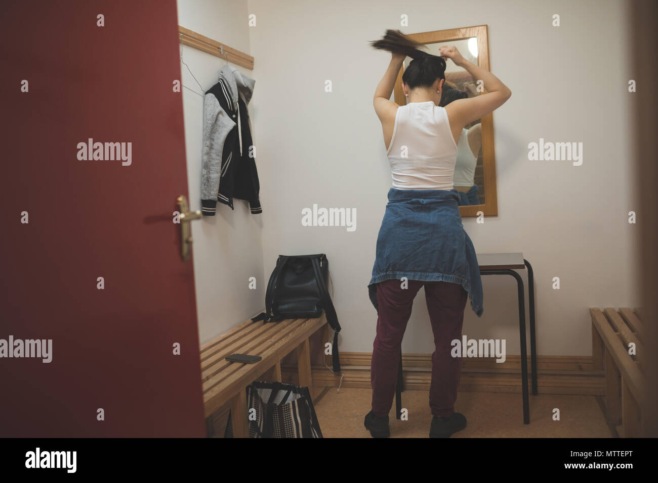 Female dancer tying her hair in changing room - Stock Image