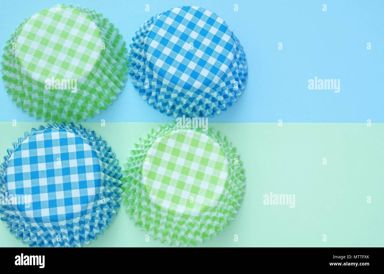 four cupcake molds of paper, arranged in a square. baking background in blue and green pastel colors. top view and text space. - Stock Photo