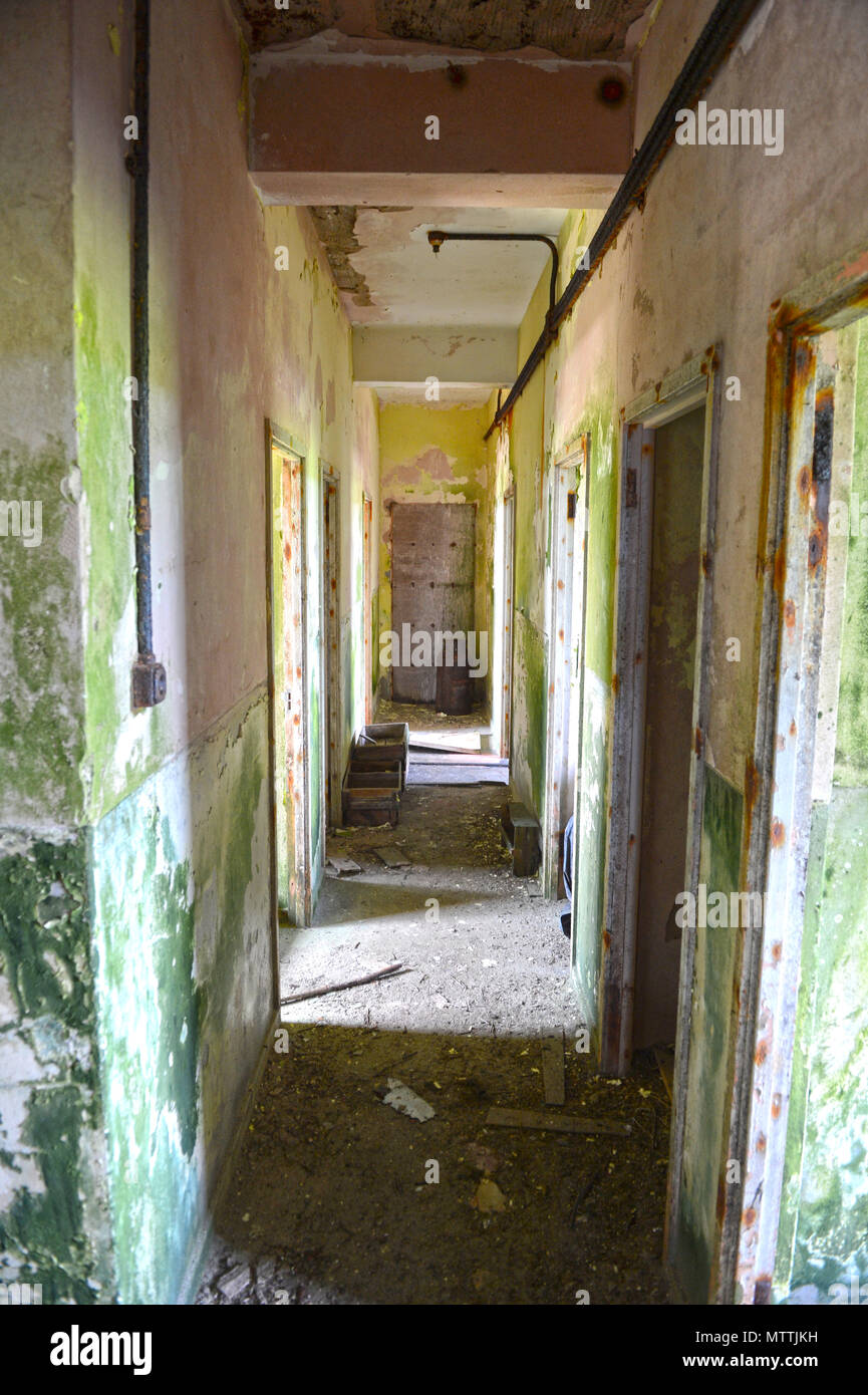 Inside an old derelict vandalised building with paint peeling graffiti and total desolation with broken glass windows and no doors - Stock Image