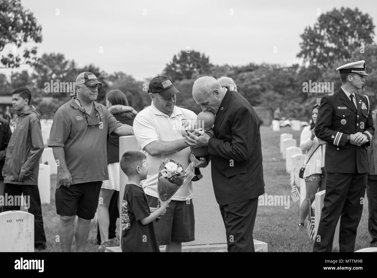 Chief of Staff John Kelly (right) kisses the head of a visitor's child in Section 60 of Arlington National Cemetery, Arlington, Virginia, May 28, 2018. Following the Memorial Day Observance at the Memorial Amphitheater, Kelly came to Section 60 with his wife, Karen Hernest Kelly, to visit the gravesite of their son, U.S. Marine Corps 1st Lt. Robert Michael Kelly. Chief of Staff Kelly also spoke with other visitors, friends, and family members visiting gravesites in Section 60.(U.S. Army photo by Elizabeth Fraser / Arlington National Cemetery / released) (This image was created in color and cha - Stock Image