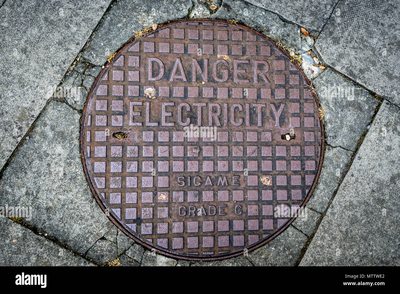 Danger electricity metal manhole cover - Stock Image