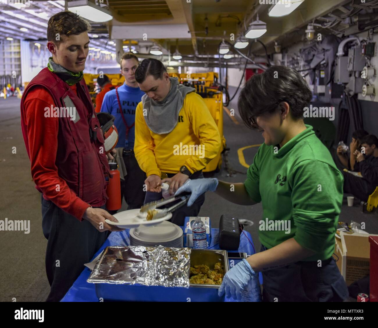 180516-N-AC117-0086 WATERS SOUTH OF JAPAN (May 16, 2018) Culinary Specialist Seaman Kate Millanayala, from Las Vegas, serves food in the hangar bay of the Navy's forward-deployed aircraft carrier, USS Ronald Reagan (CVN 76), during a replenishment-at-sea with Military Sealift Command (MSC) dry cargo/ammunition ship USNS Cesar Chavez (T-AKE 14), May 16, 2018. The non-combatant, civilian-crewed ship, operated by MSC, provides fuel, food, ordnance, spare parts, mail and other supplies to Navy ships throughout the world. Ronald Reagan, the flagship of Carrier Strike Group 5, provides a combat-read - Stock Image