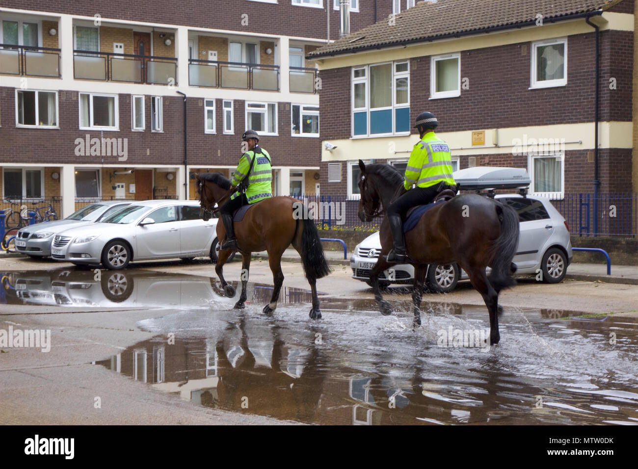 Two Metropolitan Policemen riding horses that are trotting through a puddle on the way to the stables in Bow, Tower Hamlets, London - Stock Image
