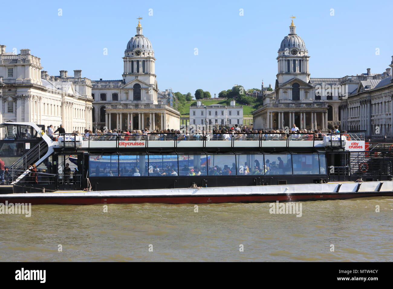 River Thames cruise boat in front of the Old Royal Naval College in hsitoric Greenwich, SE London, Emgland, UK - Stock Image