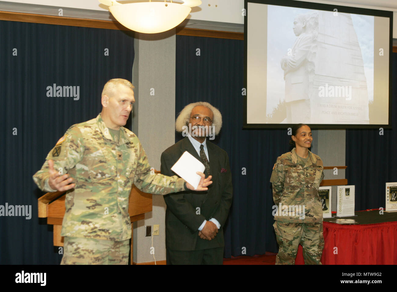 Garrison Commander Col. David J. Pinter Sr. provides closing remarks as Dr. Floyd Rose of Madison, Wis., and Master Sgt. Freida Carter, Fort McCoy equal opportunity adviser, look on during the Fort McCoy observance of Martin Luther King Jr. Day on Jan 12, 2017, at McCoy's Community Center. Rose served as the guest speaker for the event. He is a businessman who's worked for more than 40 years to evaluate, analyze, and develop policy for private- and public-sector organizations concerning sales growth, procurement practices, human-resource management, and policy. He holds leadership positions in Stock Photo