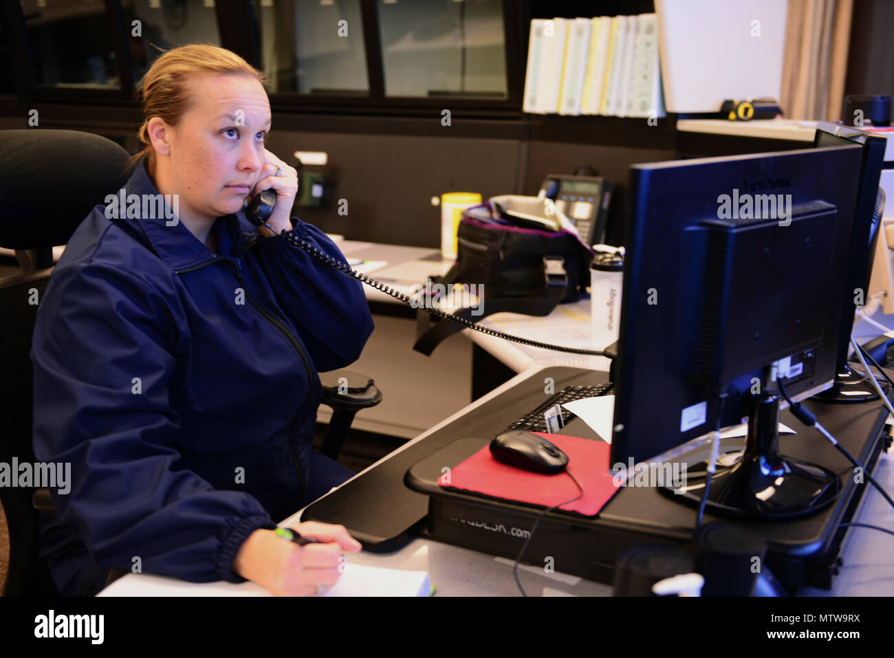 Chief Petty Officer Nichole Vital stands a 12-hour watch on duty as an operations specialist in the 13th Coast Guard District Command Center, Jan. 9, 2017. Vital is one of the few Coast Guard men and women who are responsible for monitoring a multi-mission communication platform and responding to a variety of cases from search and rescue or law enforcement case execution, to combat information center operations or intelligence gathering. U.S. Coast Guard photo by Petty Officer 2nd Class Ali Flockerzi. - Stock Image