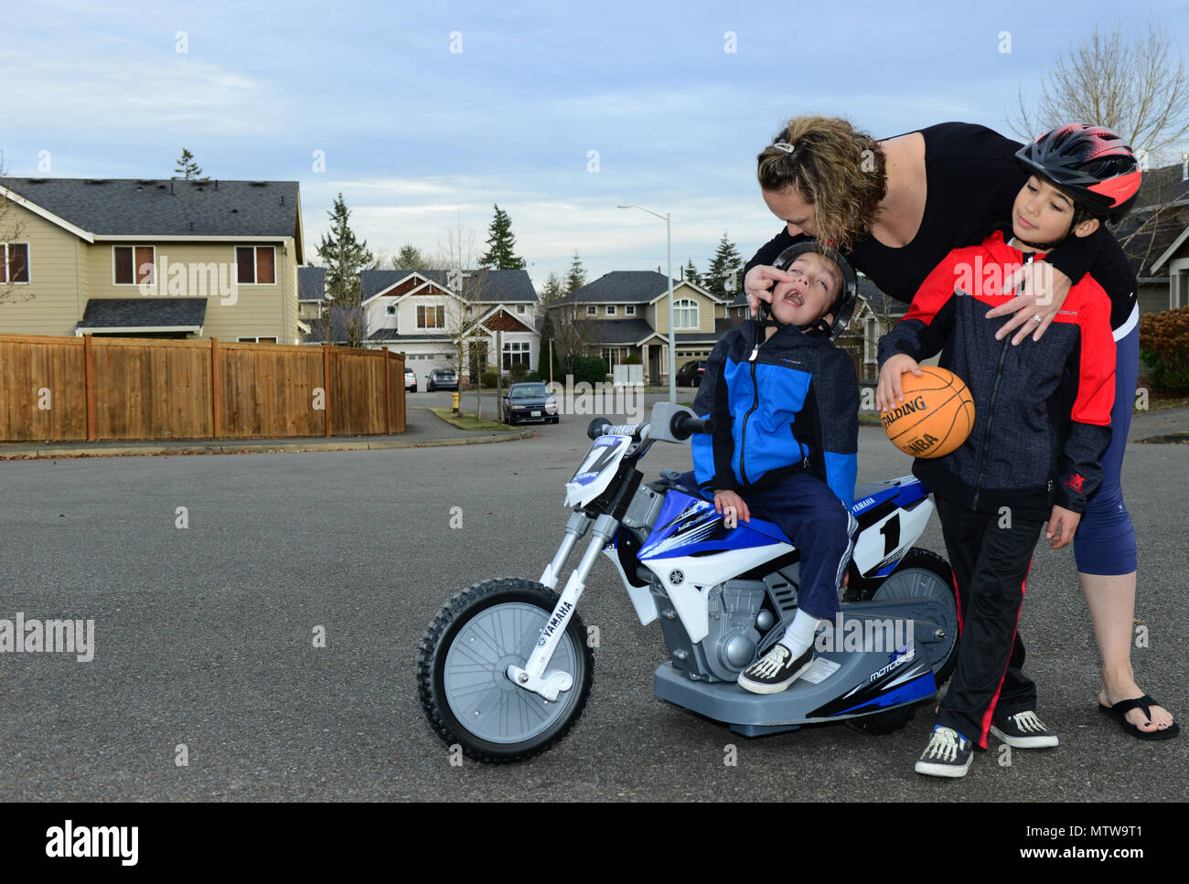 Coast Guard Chief Petty Officer Nichole Vital plays with her kids, Noah and Ethan, outside their home in Bothell, Wash., Jan. 16, 2017. Noah, 5, and Ethan, 7, both have special needs, making Vital's ability to have a balanced work life routine a little difficult. U.S. Coast Guard photo by Petty Officer 2nd Class Ali Flockerzi. - Stock Image