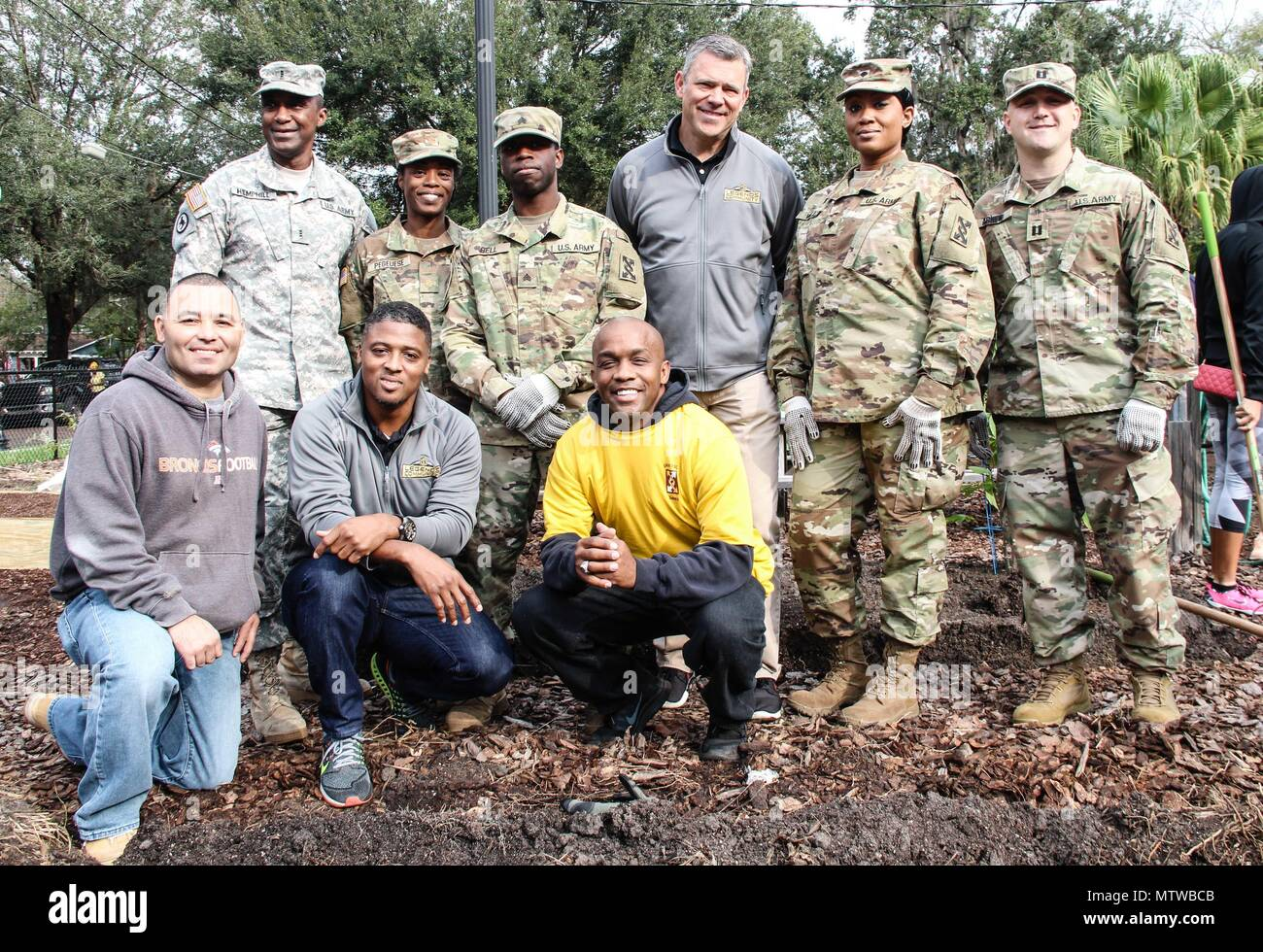 Soldiers from the 143d Sustainment Command (Expeditionary) pose for a group photo with National Football League legends Mark Brunell (top row, third from right) and Warrick Dunn (bottom row, second from left) Jan. 27, 2017, at the Colonialtown North Community Garden in Orlando, Fla. The Army Reserve and the NFL joined forces to lighten the environmental impact produced the first ever Pro Bowl to take place in Orlando by bringing one of the city's oldest community gardens back to its former, greener glory. The players and Soldiers worked side-by-side with scores of other volunteers from Central - Stock Image