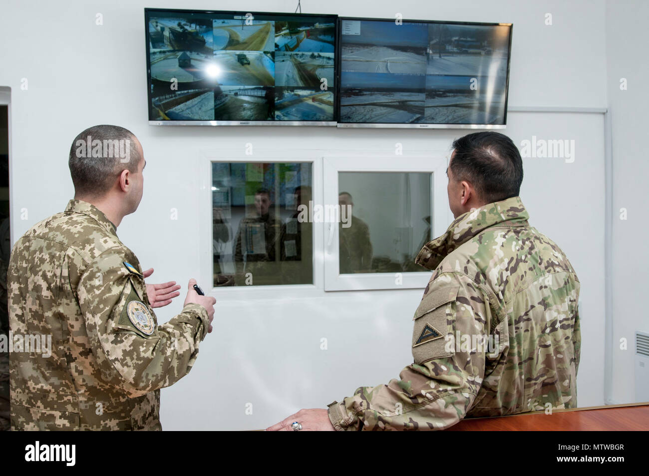 Ukrainian army Maj. Oleg Meder, a range operations officer for the International Peacekeeping and Security Center, near Yavoriv, Ukraine, shows U.S. Army Brig. Gen. Tony Aguto, commander for the 7th Army Training Center, the IPSC's cameras overlooking key checkpoints used to control the flow of traffic around the base's firing ranges on Jan. 28. (Photo by Sgt. Anthony Jones, 45th Infantry Brigade Combat Team) - Stock Image