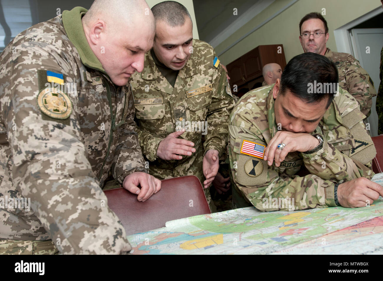 Brig. Gen. Tony Aguto, commander for the 7th Army Training Command, reviews engineering plans for the International Peacekeeping and Security Center, Near Yavoriv, Ukraine, with IPSC Commander Ukrainian army Col. Igor Slisarchuk, ISPC commander (left), and Ukrainian army Maj. Oleg Meder, IPSC range officer (center), at the IPSC range operations facility on Jan. 28. (Photo by Sgt. Anthony Jones, 45th Infantry Brigade Combat Team) - Stock Image
